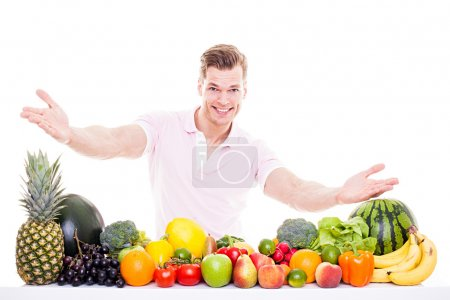 Healthy lifestyle concept - Sportive young man presenting fruits