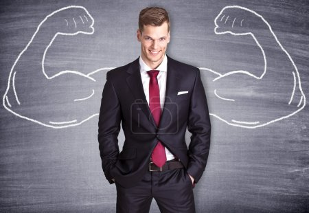 Photo for Strong Businessman with sketched arms on a blackboard - Royalty Free Image