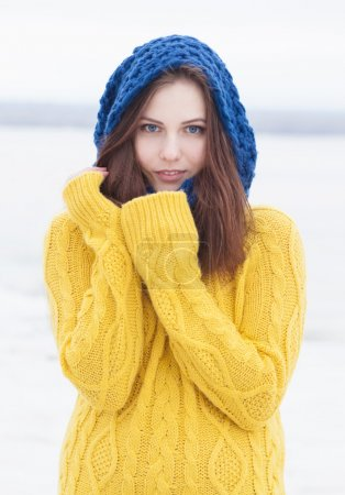 Beautiful happy girl in yellow pulloverand blue scarf