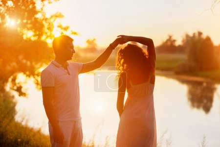 Young beautiful couple in white dancing on the background of sunset