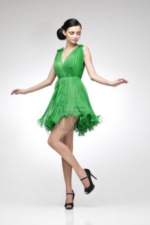 Photo pour Brune élégante en robe verte, posant en studio - image libre de droit