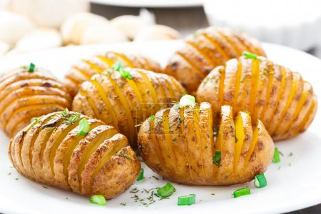 Photo for Accordion baked potatoes on a white plate - Royalty Free Image