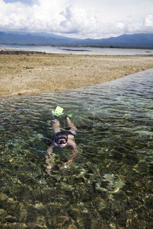 Photo pour Femme avec équipement de plongée nage sous l'eau sur l'île avec un beau fond nuageux ciel - image libre de droit