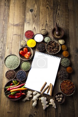 Photo for Opened cookbook with cinnamon and various spices in wooden bowls on the table - Royalty Free Image