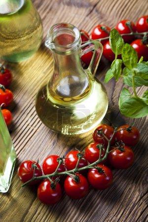 Photo pour Carafe en verre à l'huile d'olive avec des branches de tomates cerises sur table en bois gros plan - image libre de droit