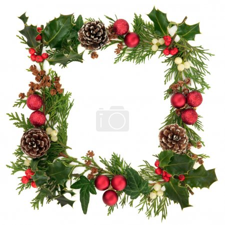 Photo for Christmas decorative border of holly, ivy, mistletoe, cedar leaf sprigs with pine cones and red baubles over white background. - Royalty Free Image