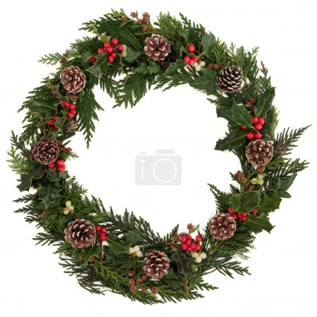 Photo for Christmas decorative wreath of holly, ivy, mistletoe, cedar and leyland leaf sprigs with pine cones over white background. - Royalty Free Image