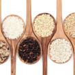 Rice varieties in olive wood spoons over white bac...