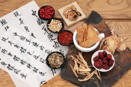 Foto de Selección de hierbas medicinales chinas tradicionales con mandarina caligrafía sobre papel de arroz sobre roble. traducción describe las funciones medicinales para aumentar la capacidad del cuerpo para mantener la salud de cuerpo y espíritu y equilibrar la energía. - Imagen libre de derechos