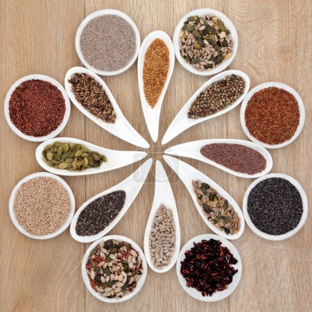Photo for Large super food seed selection in porcelain bowls over light oak background. - Royalty Free Image