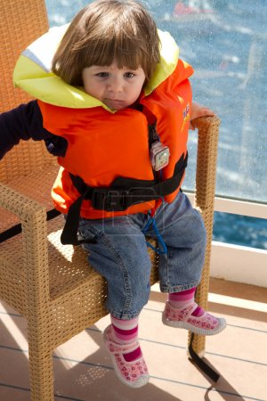 little girl dressed in life jacket stands in cabin's balcony