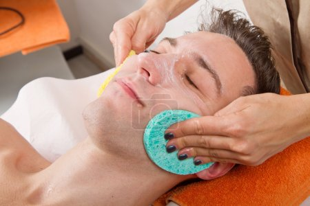 Female hands cleaning man's face in a spa center