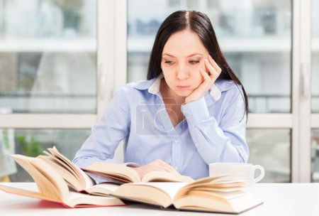 Female Student learning at home with different books