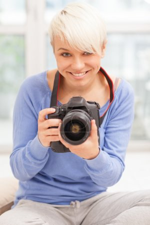 Female photographer with DSLR at home sitting on the floor