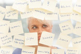 Overworked woman in front of a window full with notes
