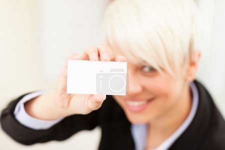 Businesswoman holding business card while smiling towards the ca