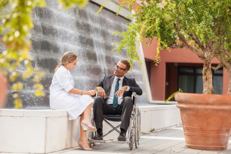 Female Doctor is talking to businessman on wheelchair