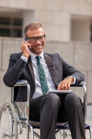 Businessman on wheelchair is phoning