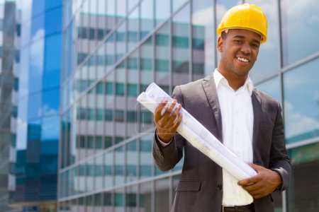 Photo pour Ingénieur de construction afro-américain devant le bâtiment tenant des plans - image libre de droit