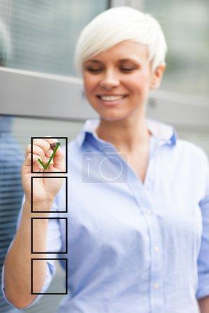 Photo pour Gestionnaire de femme blond fait une liste de contrôle - image libre de droit
