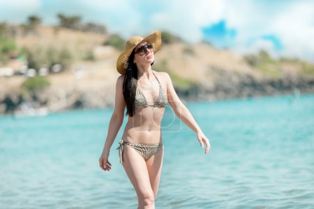 Photo for Photo of caucasian woman walking through the water at the beach - Royalty Free Image