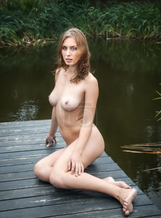 Beautiful young naked woman near a small pond