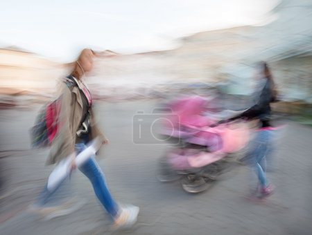 girl hurrying and women with a baby in a stroller