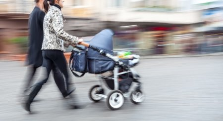 Young family with small children and a pram walking down the str