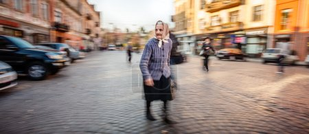 Old woman goes on her way in the early morning city