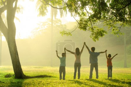 Photo for An asian family jumping in joy in the park during a beautiful sunrise, backlight - Royalty Free Image