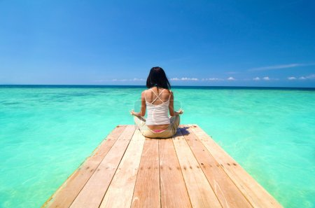 Photo for Beach yoga , asian girl on a dock - Royalty Free Image