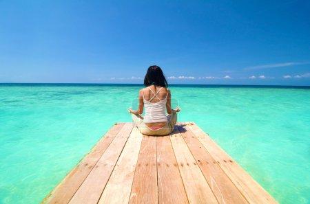 Photo pour Yoga plage, fille asiatique sur un quai - image libre de droit