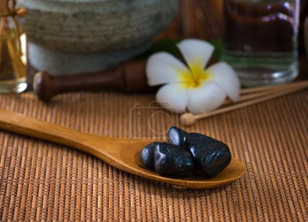hot stone massage with spa treatment items on the background
