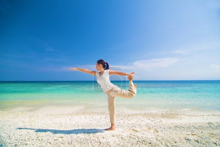 beach yoga performed by a matured asian female