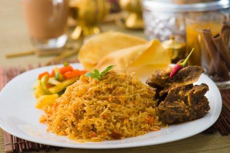 Biryani mutton rice papadam with traditional background