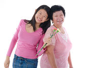 Happy Asian Chinese Mother and Daughter with carnation flower wi