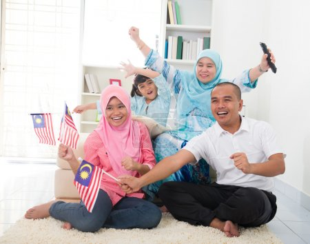 Malaysian family celebrating while watching television over a to