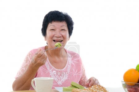Photo for Chinese senior female eating with isolated white background - Royalty Free Image