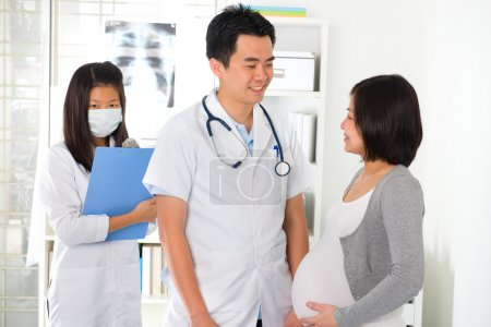 Asian doctor performing pregnancy medical check up