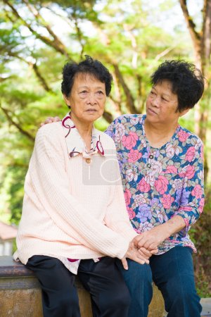 Photo for Crying Asian senior mother with her senior daughter at outdoor park - Royalty Free Image