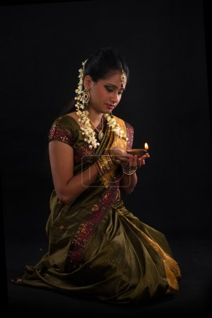 Traditional indian woman with oil lamp during the celebration of