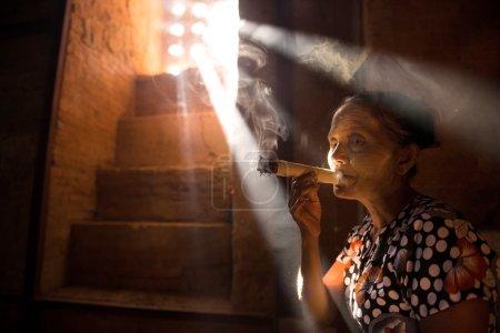 Old woman smoking cigars i