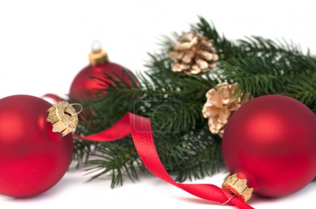 Three red christmas balls and fir, isolated on white