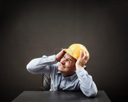 Photo pour Ingénieur peur de quelque chose d'énorme sur le point de s'effondrer sur sa tête - image libre de droit