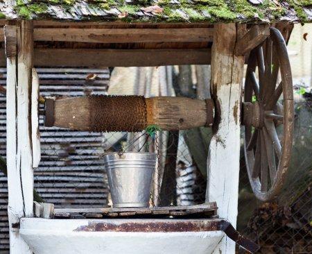 Photo pour Gros plan d'un puits avec roue, poulie et godet en aluminium - image libre de droit