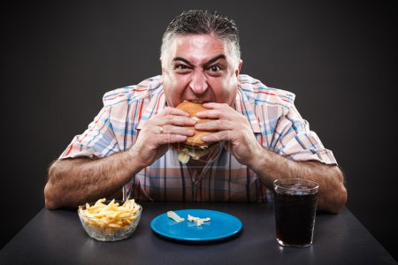 Photo for Portrait of a greedy fat man eating burger on gray background - Royalty Free Image