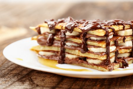 Photo for Stack of pancakes with banana slices and chocolate syrup on a plate - Royalty Free Image