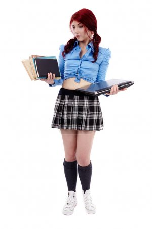Young schoolgirl choosing between books and laptop