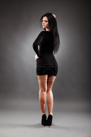 Photo for Rear view of sexy young brunette, in full length pose, on gray background - Royalty Free Image