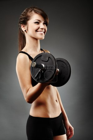 Beautiful woman lifting dumbbell